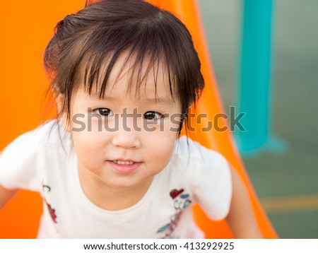Happy kid, asian baby child playing on playground - stock photo