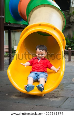 Happy kid, asian baby child playing on slide on colorful playground in the park - stock photo