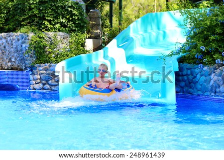 Happy kid, blonde caucasian boy, having fun floating and sliding in water park on inflatable ring enjoying sunny summer vacations in tropical resort - stock photo