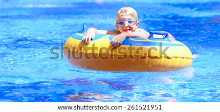 Happy kid, blonde caucasian boy, having fun floating and sliding in waterpark on inflatable ring enjoying sunny summer vacations in tropical resort - stock photo