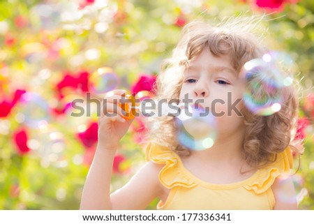 Happy kid blowing soap bubbles outdoors in spring park - stock photo