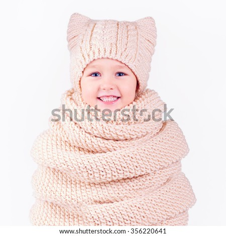 happy kid, boy covered in volume knitted scarf and hat