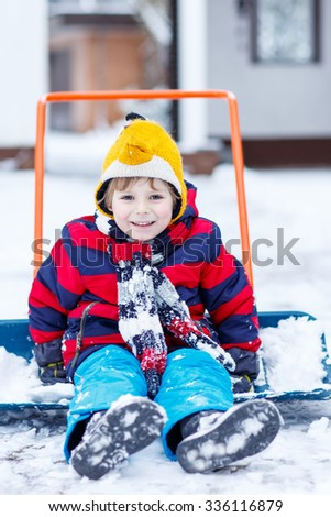 Happy kid boy having fun with riding on snow shovel , outdoors  on cold day. Active outdoors leisure with children in winter.