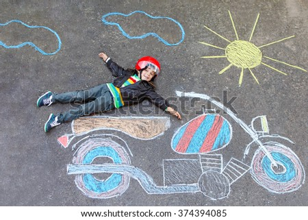 Happy kid boy in race helmet having fun with motorcycle picture drawing with colorful chalks. Children, lifestyle, fun concept. Creative leisture for kids - stock photo