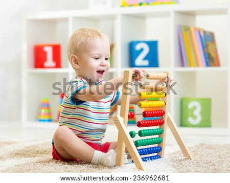 happy kid boy playing with abacus toy indoors - stock photo