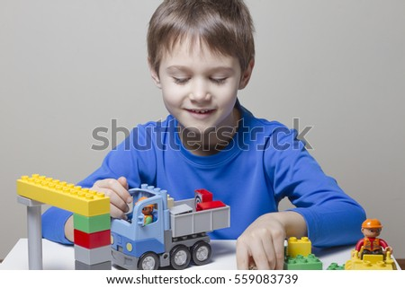 Happy kid boy playing with colorful plastic construction bricks at the table