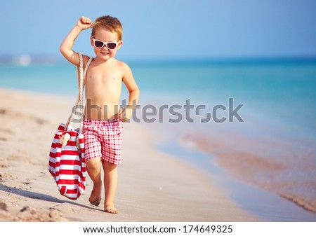 happy kid boy walking the summer beach - stock photo