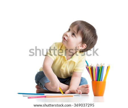 Happy kid drawing with pencils in album - stock photo