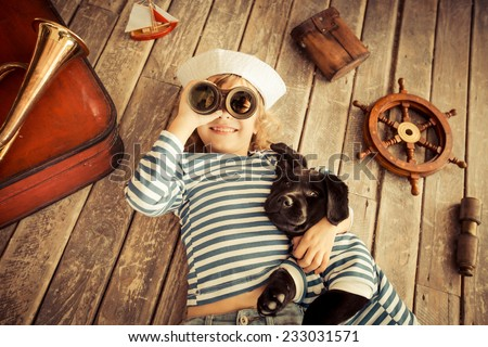 Happy kid dressed in sailor. Child playing with dog. Baby having fun at home. Travel and adventure concept. Unusual high angle view portrait - stock photo