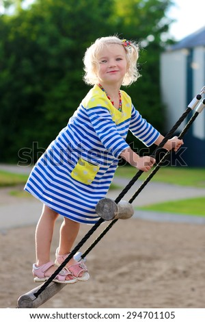 Happy kid enjoying active summer vacation. Adorable little child, blond cute toddler girl, having fun outdoors climbing on playground in the park on a sunny day - stock photo