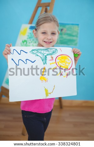 Happy kid enjoying arts and crafts painting at their desk - stock photo