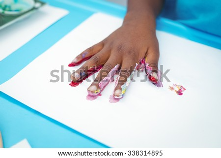 Happy kid enjoying painting with his hands at their desk - stock photo