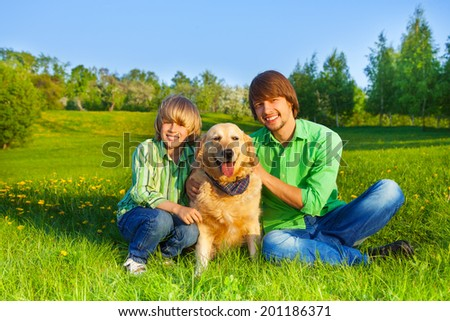 Happy kid, father and dog sit in park on grass - stock photo