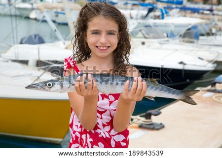 Happy kid fisherwoman with barracuda fish catch in Mediterranean marina - stock photo