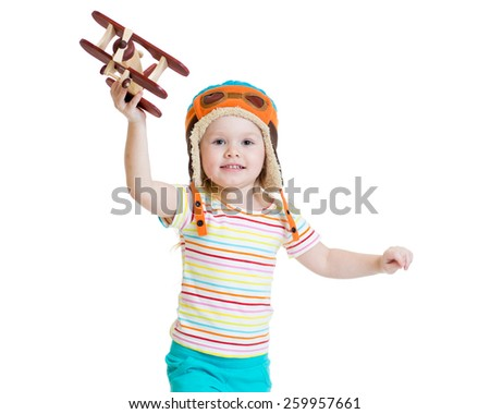 happy kid girl dressed pilot and playing with wooden airplane toy - stock photo