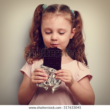 Happy kid girl eating health dark chocolate with pleasure and closed eyes. Vintage portrait - stock photo