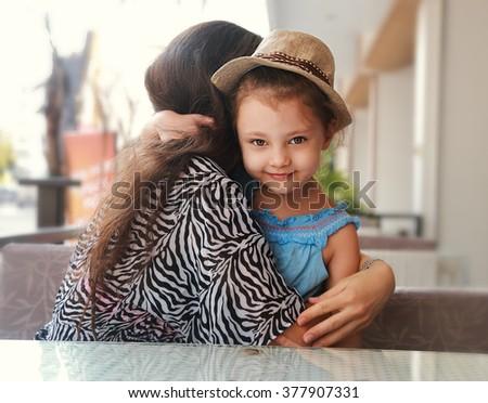 Happy kid girl embracing her beautiful mother outdoor summer background - stock photo