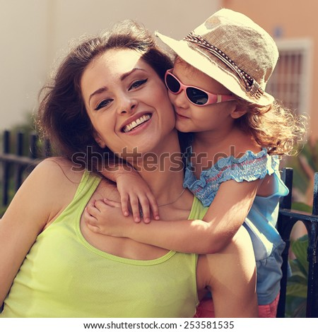 Happy kid girl embracing her smiling mother summer outdoors. Closeup vintage portrait - stock photo