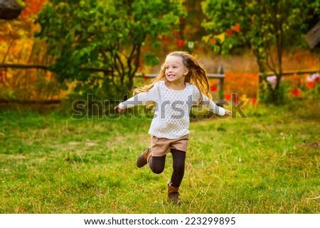 Happy kid girl having fun the autumn park. - stock photo