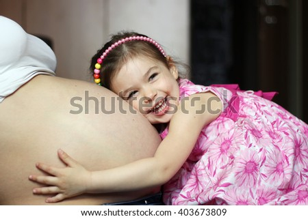 Happy kid girl hugging pregnant mother's belly, pregnancy and new life concept - stock photo
