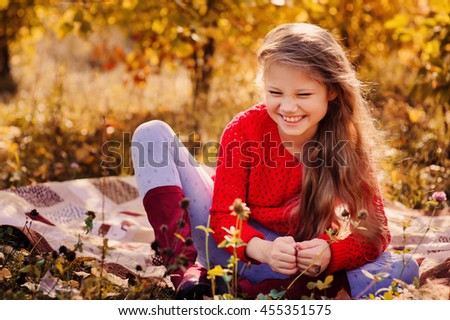 happy kid girl in red sweater having fun on autumn picnic, sitting on cozy blanket - stock photo