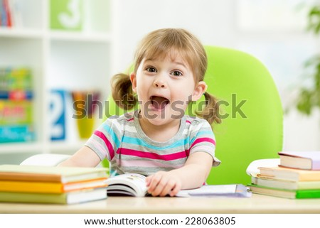 Happy kid girl reading book at table in nursery - stock photo