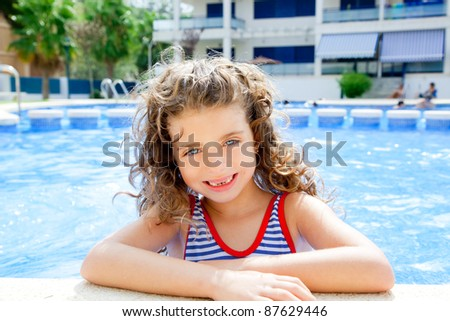 happy kid girl smiling at swimming pool in summer vacation - stock photo