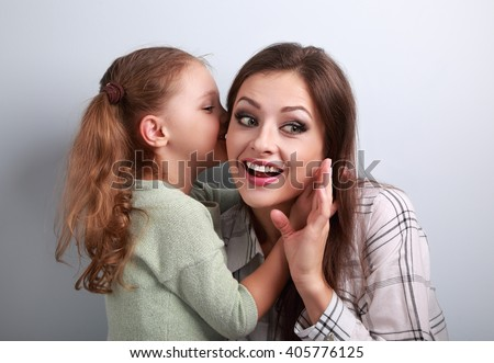 Happy kid girl whispering the secret to her surprising mother in ear with fun face on blue background - stock photo