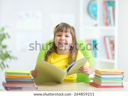 Happy kid girl with opened book in primary school - stock photo