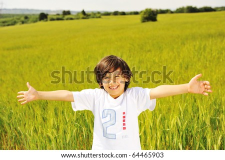 happy kid in nature, positive smiling child on green beautiful meadow with open arms looking in camera - stock photo