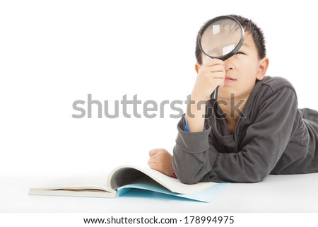 happy kid is holding magnifying glass to explore  - stock photo