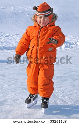 happy kid on skate in the outdoor rink - stock photo