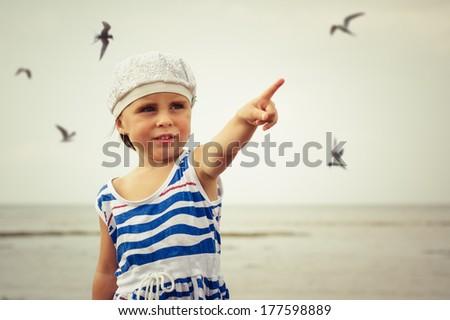 Happy kid on the beach with birds. - stock photo