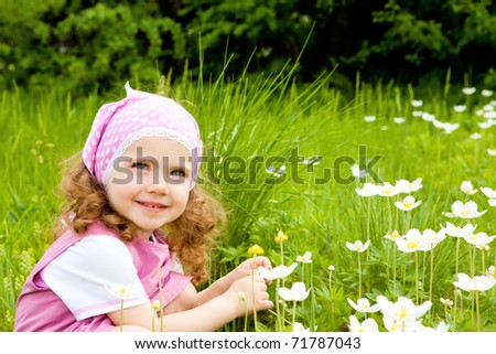 Happy kid on the meadow with white flowers - stock photo