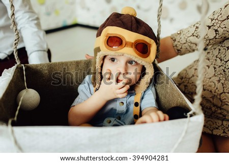 Happy kid playing and picking his nose in handmade basket of air balloon. Child having fun at home with parents. Young pilot indoors. Boy in hat like a helmet looking left. - stock photo