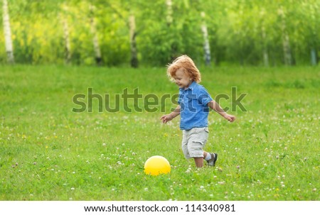 happy kid playing football and ready to kick the ball - stock photo