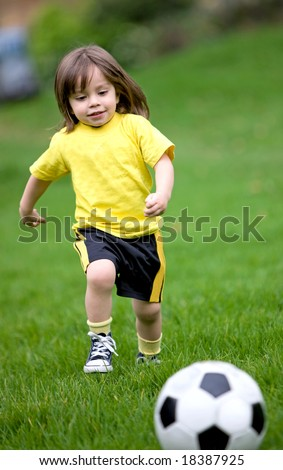 happy kid playing football in a park outdoors - stock photo