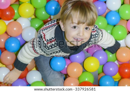 Happy Kid Playing with balls at kindergarten - stock photo