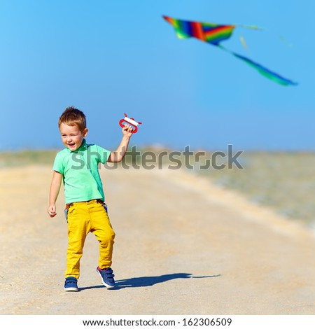 happy kid playing with kite on summer field - stock photo