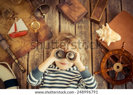Happy kid playing with nautical things. Child having fun at home. Travel and adventure concept. Unusual top view portrait - stock photo