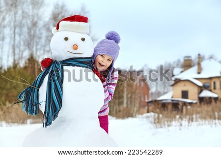 happy kid playing with snowman in santa hat. funny little girl on a walk in the winter outdoors - stock photo