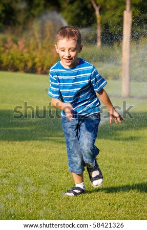 Happy kid playing with sprinkling water - stock photo