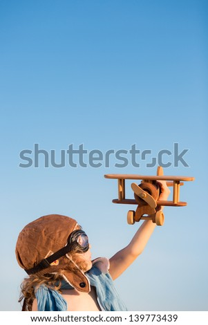 Happy kid playing with toy airplane against blue summer sky background. - stock photo