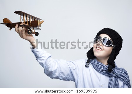 Happy kid playing with toy airplane against gray background - stock photo