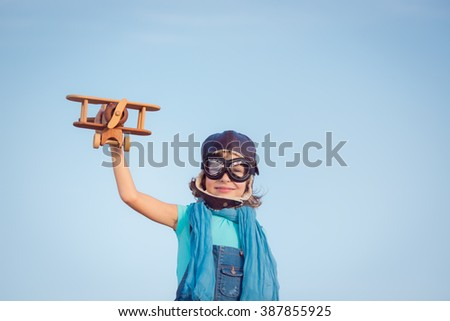 Happy kid playing with toy airplane against summer sky background. Travel concept