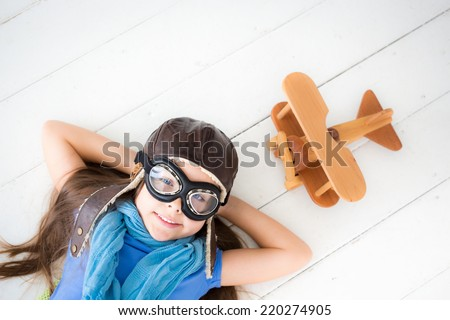 Happy kid playing with toy airplane. Kid lying on wooden floor at home - stock photo
