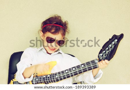 Happy kid playing with toy guitar. retro filter. hand in motion. - stock photo