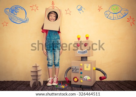 Happy kid playing with toy robot at home. Innovation technology and success concept - stock photo