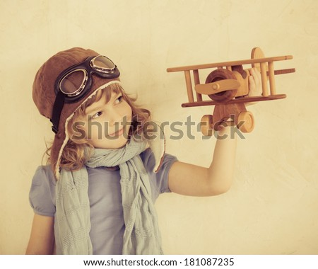 Happy kid playing with toy wooden airplane indoors - stock photo