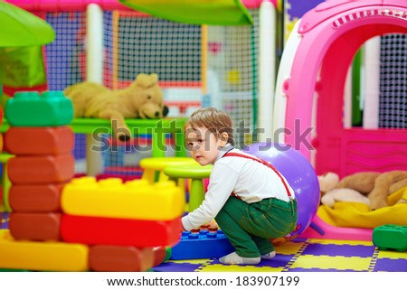 happy kid playing with toys in kindergarten - stock photo